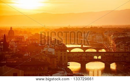 Bridges the arno river in florence italy old town evening sunset with sun light through golden smoke of mist