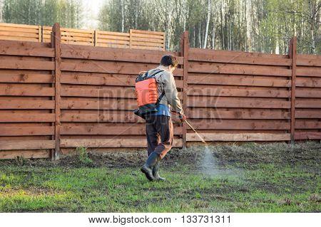 Man Sprays Grass With Herbicide Of A Knapsack Sprayer
