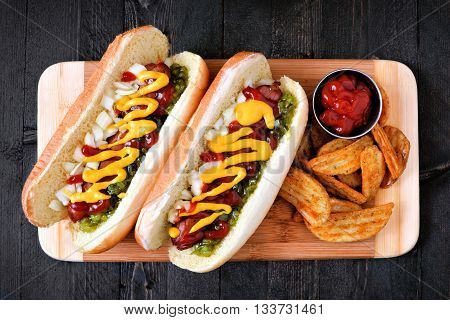 Two Hot Dogs Fully Loaded With Toppings And Potato Wedges On Wooden Board, Overhead View