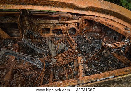 Rusty burnt out car showing inside devastation caused by fire