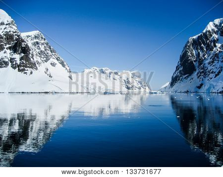 Breathtaking scenery with snow capped mountains reflected in the clear blue waters of the Lemaire Channel Antarctica