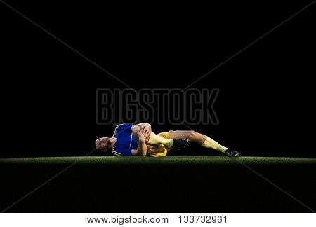 Professional young football to experience pain lying on grass on black background
