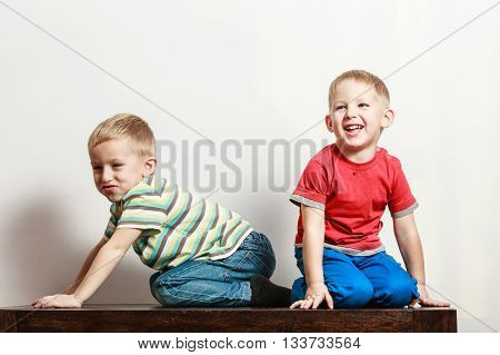 Free time fun and independence. Little boys play together indoors sit on table. Blonde children wear colorful clothes.