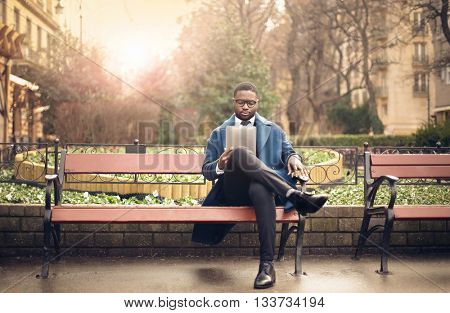 Elegantly dressed businessman reading on a tablet
