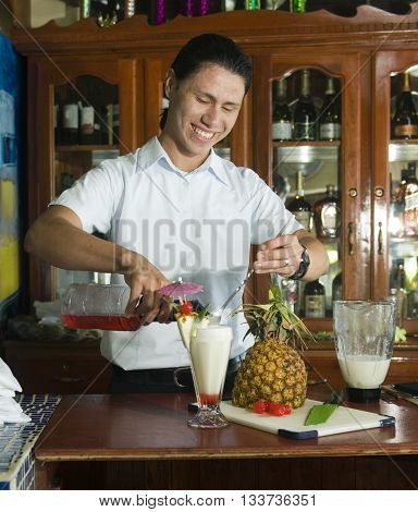 Big Corn Island, Nicaragua-April 2: Bartender mixing fresh pineapple drink at bar in hotel in  Corn Island, Nicaragua Central America on April 2 2014.
