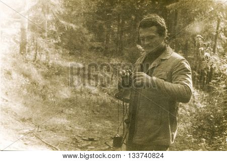 LODZ, POLAND, CIRCA 1970's: Vintage photo of young man with a camera and a light meter taking photos outdoor