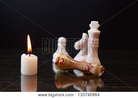 Chess King made from Onyx lying near other chessmen near lighting candle