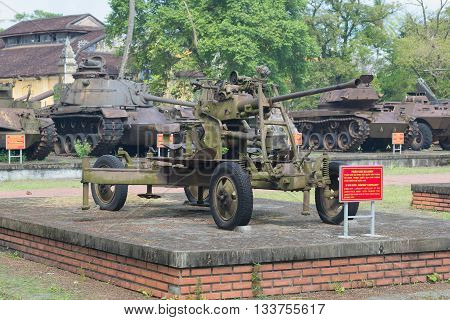 HUE, VIETNAM - JAN 08, 2016: 37-mm anti-aircraft gun in the background of American armored vehicles of the period of the Vietnam war in Hue, Historical landmark of the city Vietnam