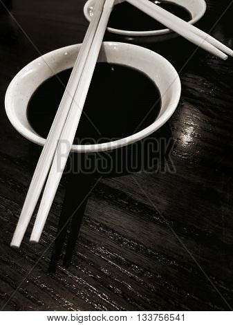 Japanese sushi chopsticks with soy sauce bowl on black wooden background