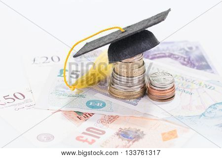 Mortarboard on a stacked of coins close up
