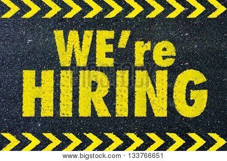 we're hiring yellow word on road background