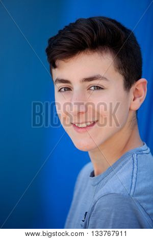 Portrait of a teenager rebellious man with a blue background
