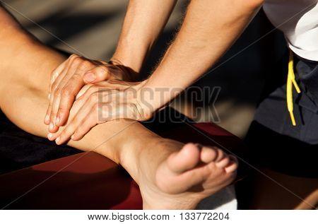 Sports massage. Therapist is giving a leg massage.