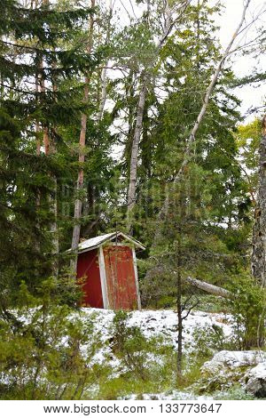 A old rustic outhouse in a forest. Early spring in Porkkala Finland. Little snow on the ground.