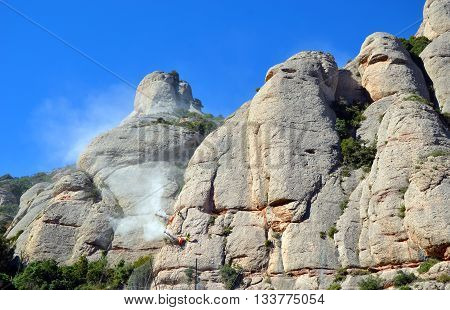 Workmen drilling and securing the limestone of the Mountains of Montserrat, Catalonia, Spain