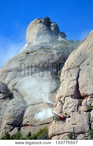 Workmen abseiling and drilling the limestone cliffs of the Mountains of Montserrat, Catalonia, Spain