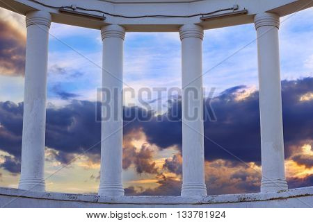 View on dramatic cloudy sunset sky through the greek columns