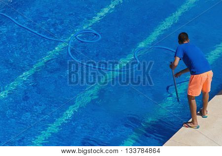 Worker Cleaning The Swimming Pool