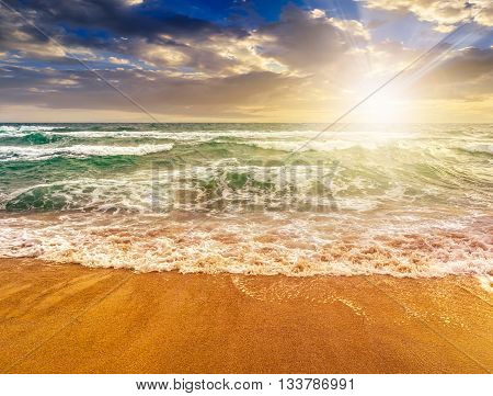 Sea ​​waves Running On Sandy Beach At Sunset