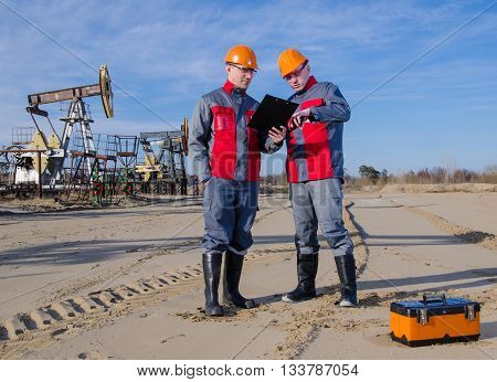 Workers in the oilfield one holding radio in his hand. Pumpjack and wellhead background. Toolbox foreground. Oil and gas concept.