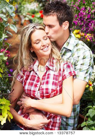 Young happy love couple smiling in the garden