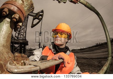 Woman engineer in the oil field repairing wellhead with the wrench wearing orange helmet and work clothes. Oil and gas concept. Fish eye shot. Toned.
