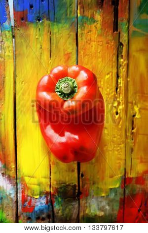 Photo of red pepper on yellow wooden background