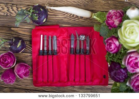 Carving knives with carved bouquet on wooden background