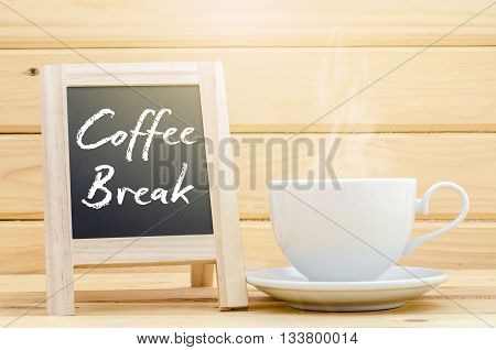 Coffee Break on chalkboard with a hot coffee cup on wood background.
