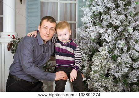 Caring father with his son posing for a joint portrait. June 19 - an international holiday Father's day. Family photo shoot in bright new year interiors
