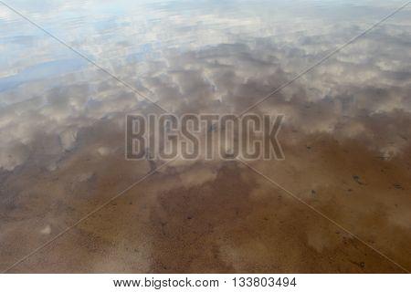 Clouds on the water surface sandbar beach