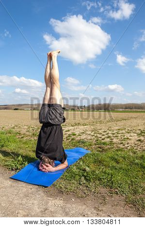 on an sunny day this man enjoys Mukta Hasta Sirsasana yoga in nature