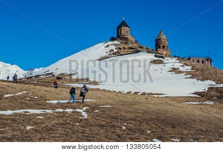 Gergeti Georgia - April 25 2015. Tourists walks near famous landmark Tsminda Sameba church (english: Holy Trinity) near Gergeti town in Georgia