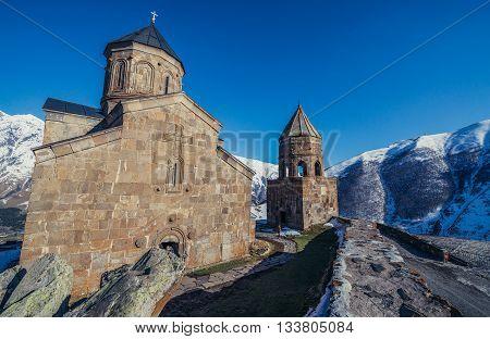 Gergeti Georgia - April 25 2015. Famous landmark Tsminda Sameba church (english: Holy Trinity) and bell tower near Gergeti town in Georgia