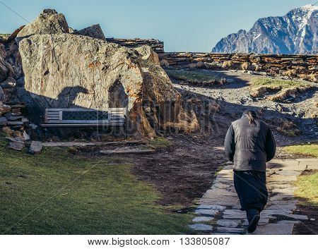 Gergeti Georgia - April 25 2015. Monk walks next to Tsminda Sameba church (english: Holy Trinity) near Gergeti town in Georgia