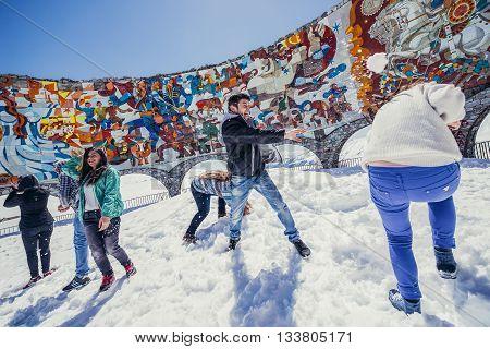 Guduari Georgia - April 25 2015. Tourists plays snowball fight in front of Soviet and Georgian Friendship monument near Guduari ski resort in Georgia