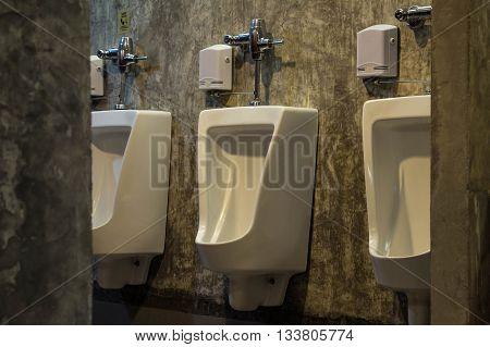 The white urinals in men's bathroom toilet