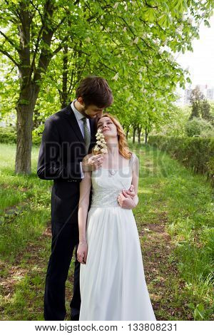 Couple bride and groom walking in the park of chestnuts