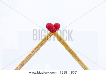 Close up matchsticks heart shaped on white background.