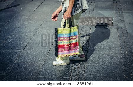 Belgrade Serbia - August 29 2015. Old woman walks with shopping bag on Prince Michael Street in Belgrade city