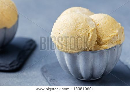 Vanilla Ice Cream with vanilla pods in metal vintage bowl. Homemade Organic product Slate background.