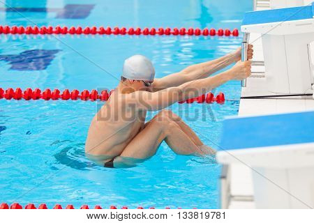 Young man in a pool - go to start swimming. backstroke during.