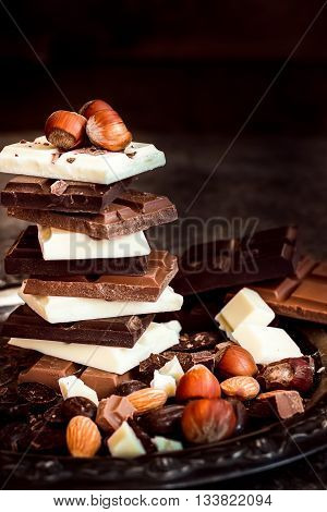 Chocolate / Chocolate bar / chocolate background/chocolate tower and nuts. Dark background. Selective focus.