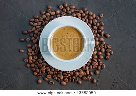 Coffee beans and cup of espresso on dark background