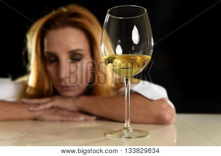 drunk blond woman alone in wasted depressed expression looking thoughtful with white wine glass isolated on black background in alcohol abuse and alcoholic housewife concept poster
