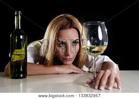 drunk blond woman alone in wasted depressed face expression looking thoughtful to white wine glass isolated on black background in alcohol abuse and alcoholic housewife concept poster