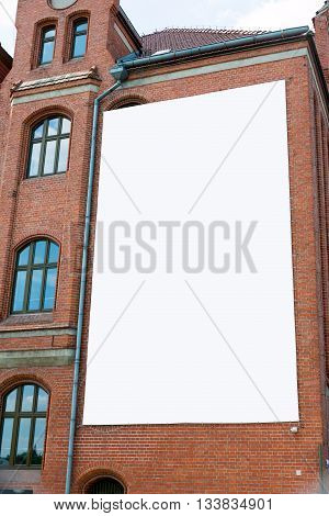 Blank billboard canvas on brick wall. Outdoor advertising in the city.