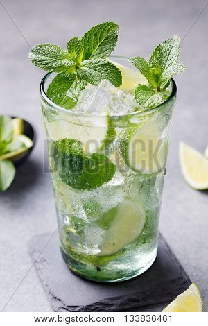 Mojito cocktail with lime and mint in highball glass on a grey stone background.