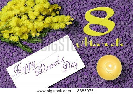 mimosa, candle and 8 march happy womens day written on violet pebbles for the international womens day