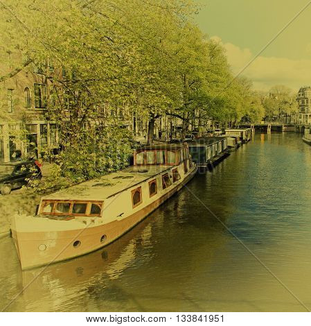 Beautiful city view with canal houseboats and traditional houses typical picture of canals in Amsterdam, Netherlands. Vintage film toned effect square image
